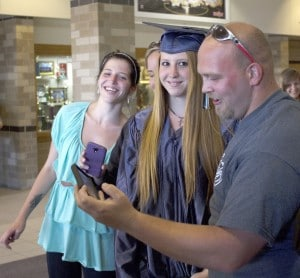 Betty Roger and her family look at a selfie they shot following the graduation ceremony of the Ombudsman class of 2014. Roger was one of 14 students who were a part of Ombudsman Montcalm Center, an alternative high school for at risk students, who graduated Tuesday night in Greenville's High School Performing Arts Center.