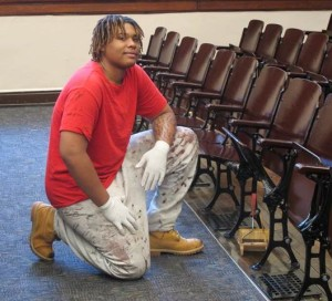 Part of the youth employment initiative, Ombudsman Chicago student, Devonte Davis, works to refinish auditorium seats and flooring at CPS McPherson Elementary School