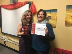 Andrea Rodriquez is on the left holding a small red plaque and her colleague is to the right of her holding a certificate of reward. Behind them is a smart board with red fabric draped over the top and a picture of a zebra.