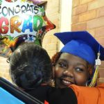 "Natchez-Adams Ombudsman School graduate hugs a family member while holding a ballon that reads ""CONGRATS GRAD"""