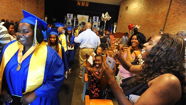 Families applaud graduates as they walk down the aisle to receive their diplomas