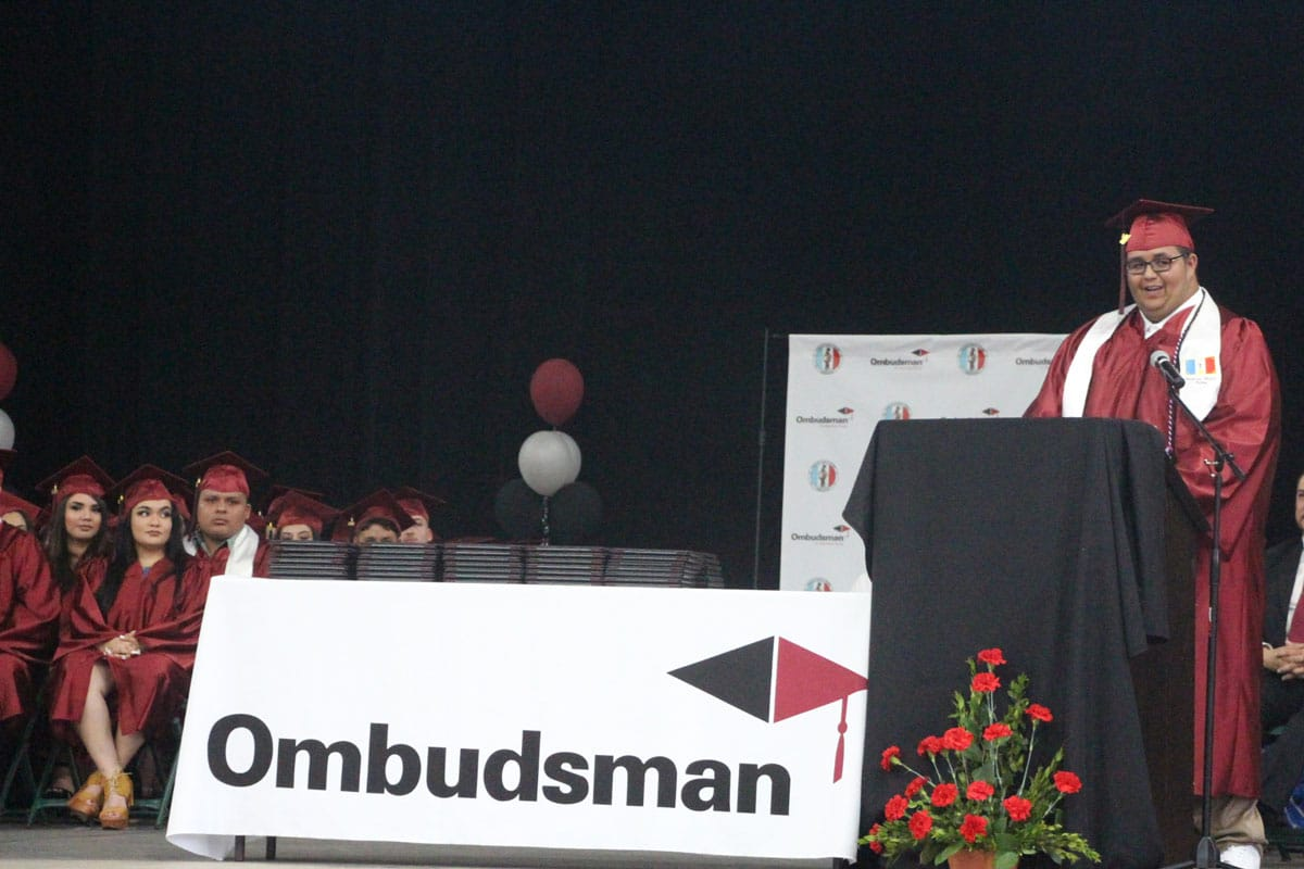 A graduate in a red robe and cap stands on stage behind a podium delivering a commencement address as other graduates look on