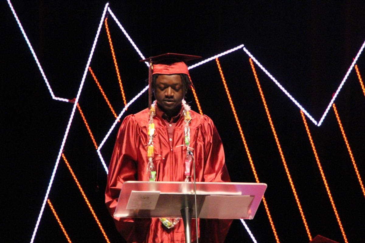 A graduate in a red robe and cap stands on stage behind a podium delivering a commencement address