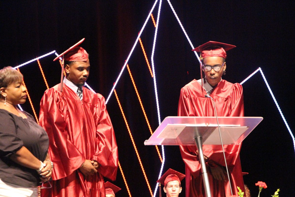 Two ombudsman arizona graduates, Kenneth Rabb (right) and Elijah Grimes (left) stand on stage behind a podium, delivering a graduation address