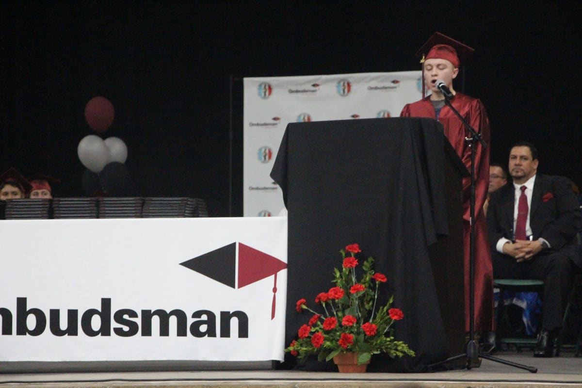 A graduate in a red robe and cap stands on stage behind a podium delivering a commencement address as other graduates and faculty look on