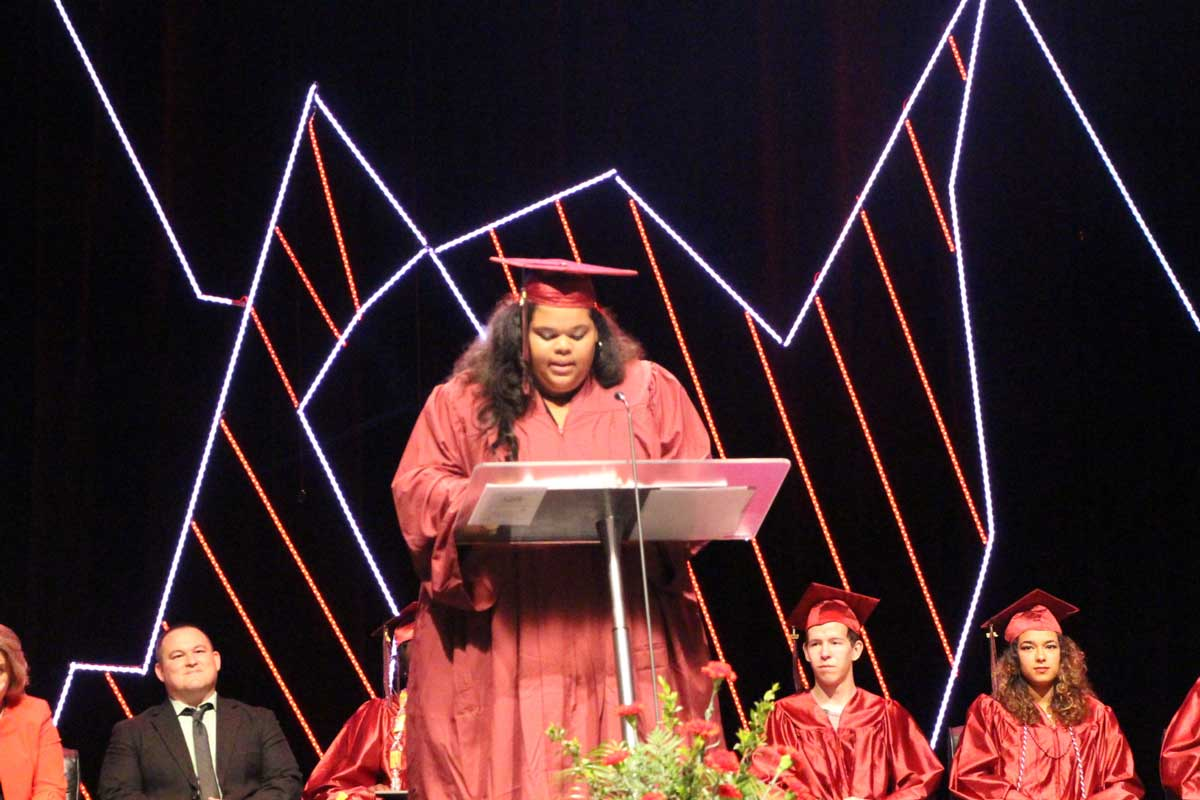 A graduate in a red robe and cap stands on stage behind a podium delivering a commencement address as other graduates and faculty, seated to the rear, look on
