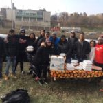 Ombudsman Chicago students and staff standing in a group behind a table with stacks of thanksgiving meals in to-go containers