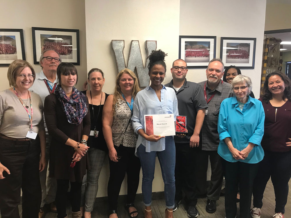 First place winner Berlyn Schulte, holds a certificate with her name on it, smiling at camera. Her colleagues stands around her, also smiling.
