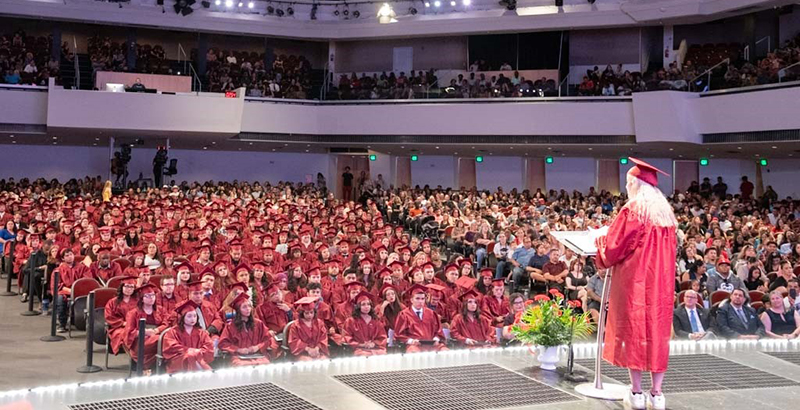 a graduate addresses an auditorium of students and family at an Ombudsman Arizona graduation ceremony