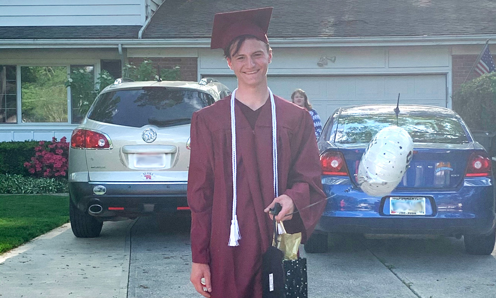 Ombudsman Graduate Zack Johnson poses for the camera, smiling. He stands in front of his home wearing a maroon graduate gown and cap.